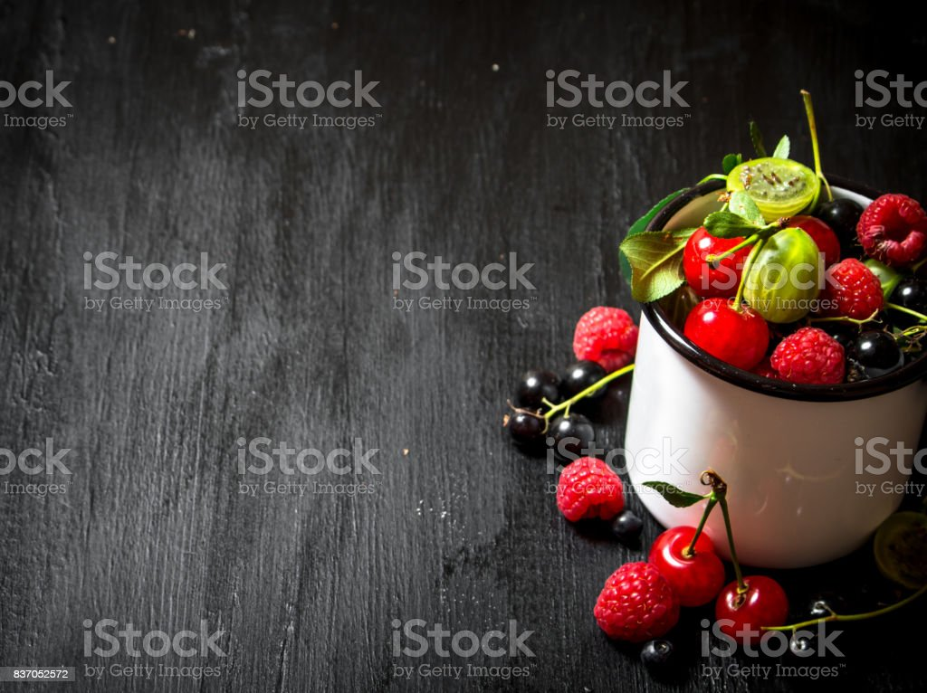 Berries in a mug. On black wooden background. stock photo