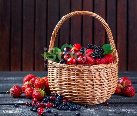 827935944 istock photo Berries mix in basket on rustic wooden background 826457066