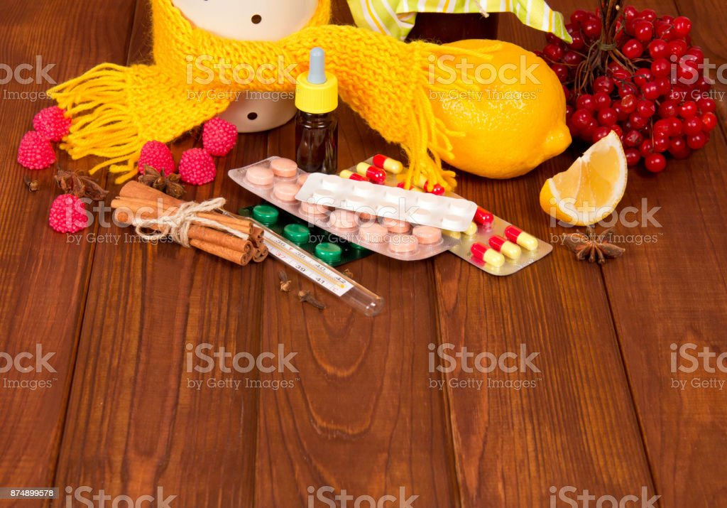 Berries of kalina, spices for tea with lemon and tablets from colds, against the background of table stock photo