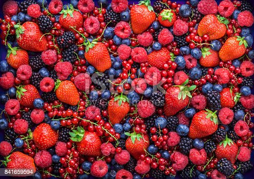 841659594 istock photo Berries overhead closeup assorted mix in studio on dark background 841659594