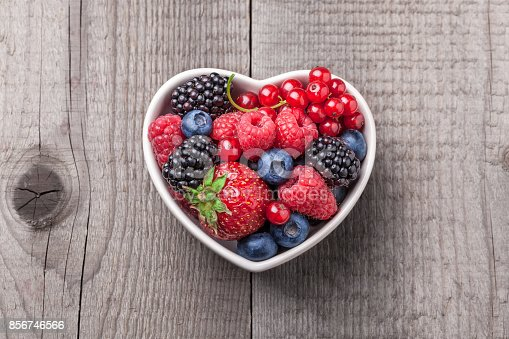 841659594 istock photo Berries overhead mix in heart shaped ceramic jar wooden background 856746566