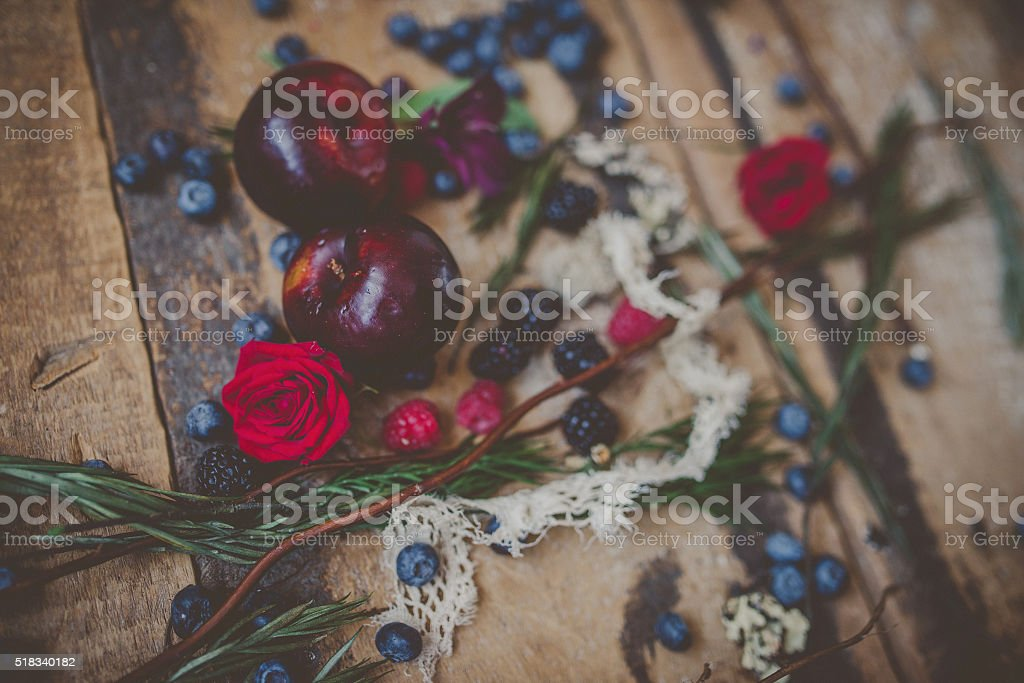 Berries, plums and avocados on barnwood stock photo