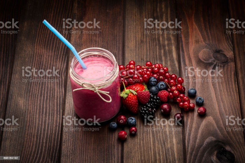 Berries smoothie in a glass jar stock photo