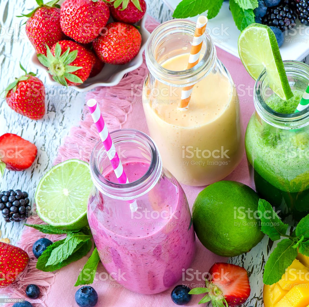 Berry and fruits smoothie in bottles, healthy summer detox yogur stock photo
