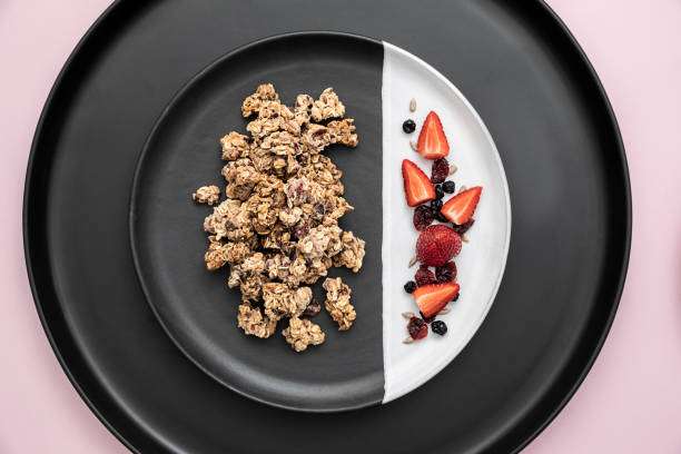 berry bliss breakfast granola/muesli clusters on plate with scattered ingredients - anthony mcgovern stock photos and pictures