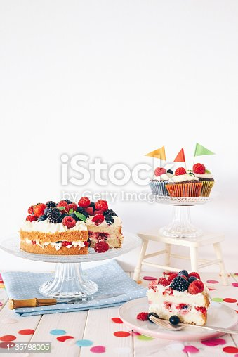 Berry cake and chocolate cupcakes with colourful confetti on white wooden table