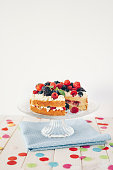 Berry cake with colourful confetti on white wooden table
