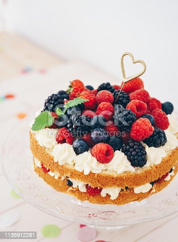 Berry cake with heart shaped sparkler and confetti on white wooden table