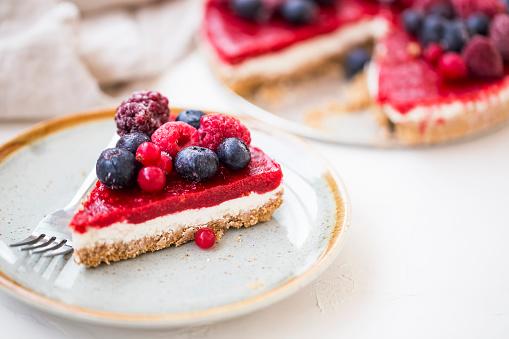 Berry cheesecake slice, fresh frozen red fruits and cheese cake slice, tasty dessert