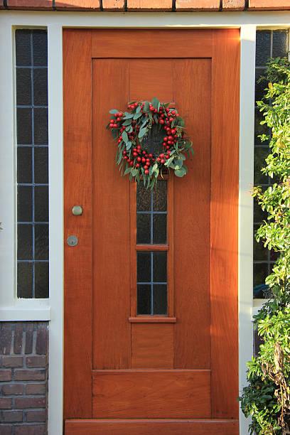 berry weihnachtskranz mit dekorationen auf einem zimmer  - türbänder stock-fotos und bilder
