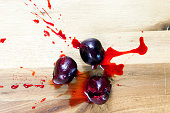 three crushed ripe cherries. on the board spreads and sprinkles red juice of berries. photo close-up, top view