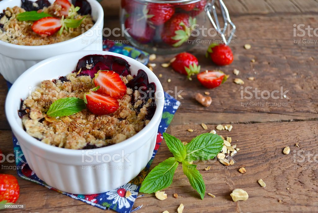 Berry crumble with oatmeal and almonds on wooden background stock photo