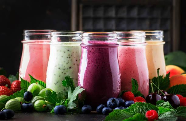 berry fruitcocktails, smoothies en milkshakes, vers fruit en bessen op bruine tafel, stilleven, selectieve focus - yoghurtdrankje stockfoto's en -beelden