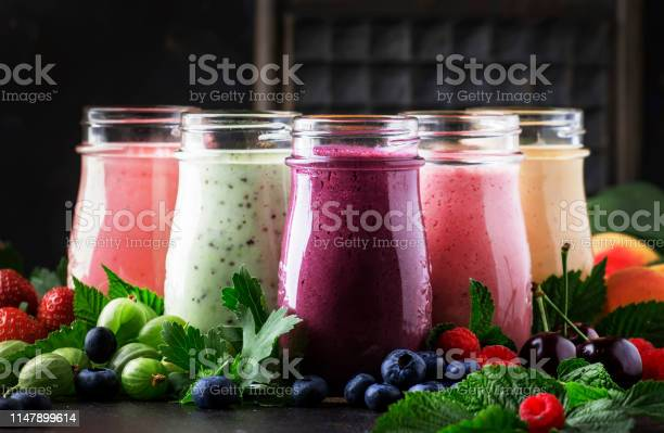 Berry Fruit Cocktails Smoothies And Milkshakes Fresh Fruit And Berries On Brown Table Still Life Selective Focus Stock Photo - Download Image Now