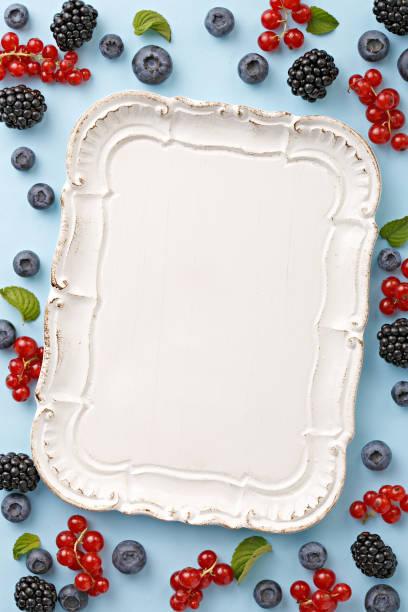 von oben betrachtet berry frucht frame auf blauem grund. beeren mit einem serviertablett. kopieren sie raum. ansicht von oben - tablett holz stock-fotos und bilder