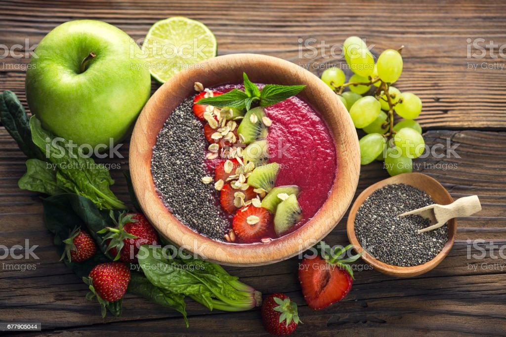 Berry fruit smoothie in the bowl with fruits and seeds royalty-free stock photo