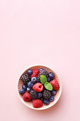 Berry (raspberry, blueberry, blackberry) fruits bowl on a pastel background. Top view. Copy space