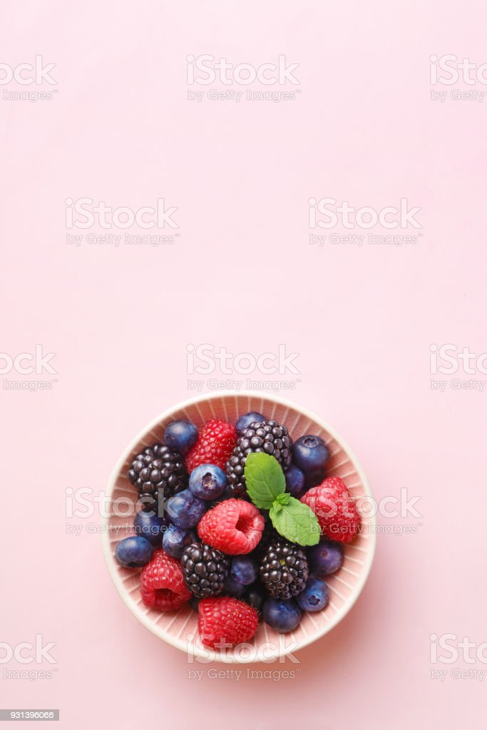 Berry (raspberry, blueberry, blackberry) fruits bowl on a pastel background. Top view. Copy space stock photo