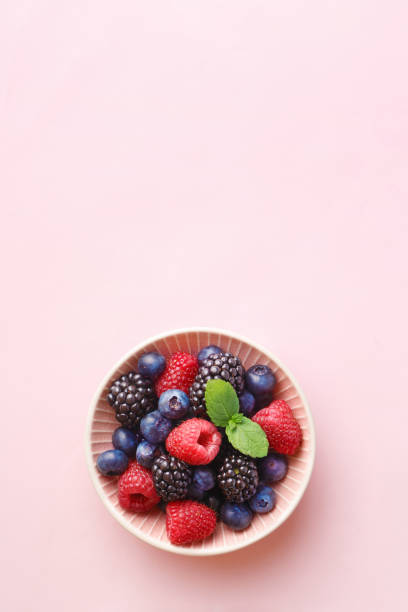 berry (raspberry, blueberry, blackberry) fruits bowl on a pastel background. top view. copy space - berry stock photos and pictures