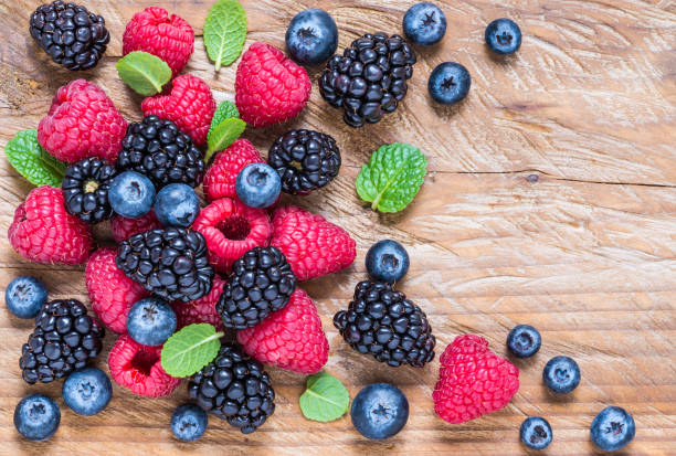 berry fruits on wooden background. - berry stock photos and pictures