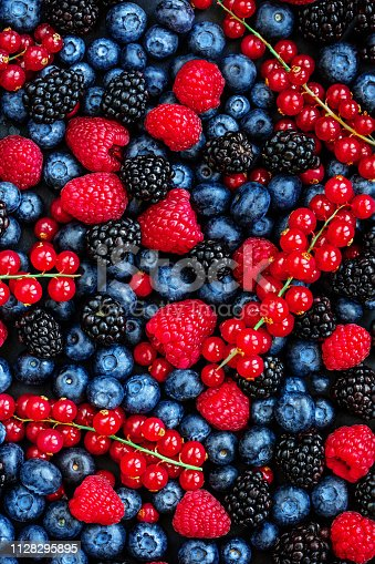 841659594 istock photo Berry Pattern. Fresh Summer Berries mix Background with Strawberry, Raspberry, Red currant,  Blueberry and Blackberry, top view 1128295895