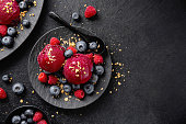 Tasty appetizing summer refreshing ice cream scoops with wild berries served on dark plate on dark background.
