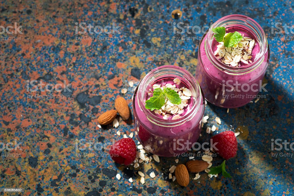 berry smoothie in a bottle and dark background, top view stock photo
