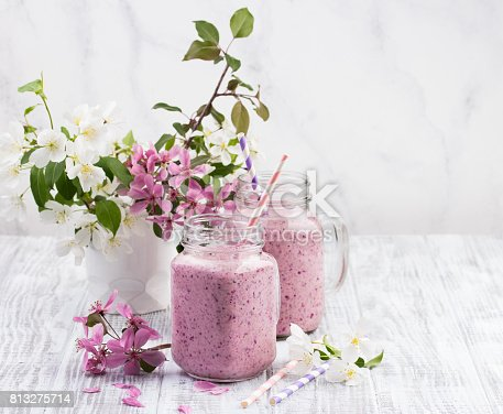 istock Berry smoothie or milkshake in jar on white wooden rustic background 813275714