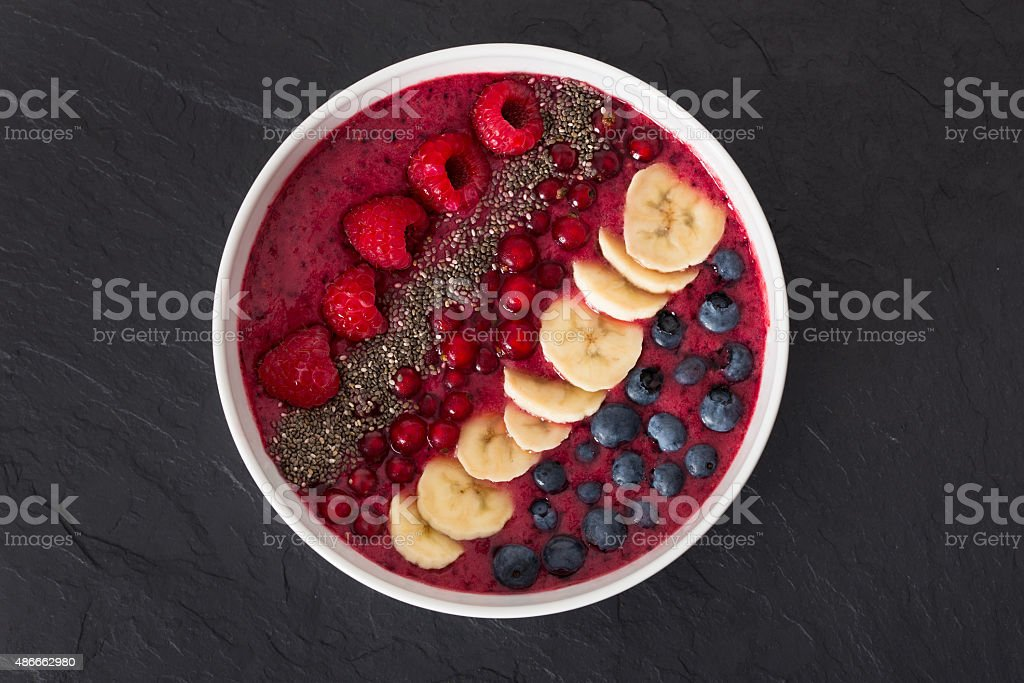 berry smoothie-bowl with chia seeds, bananas, blueberries, currant and raspberries stock photo