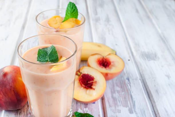 beeren-smoothies von aprikose, pfirsich und banane in gläsern und zutaten auf einem holztisch - pfirsich milchshake stock-fotos und bilder