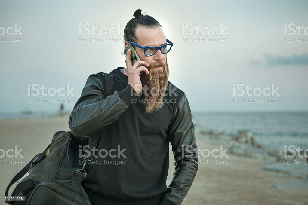 Bespectacled bearded handsome male on smartphone by the sea stock photo