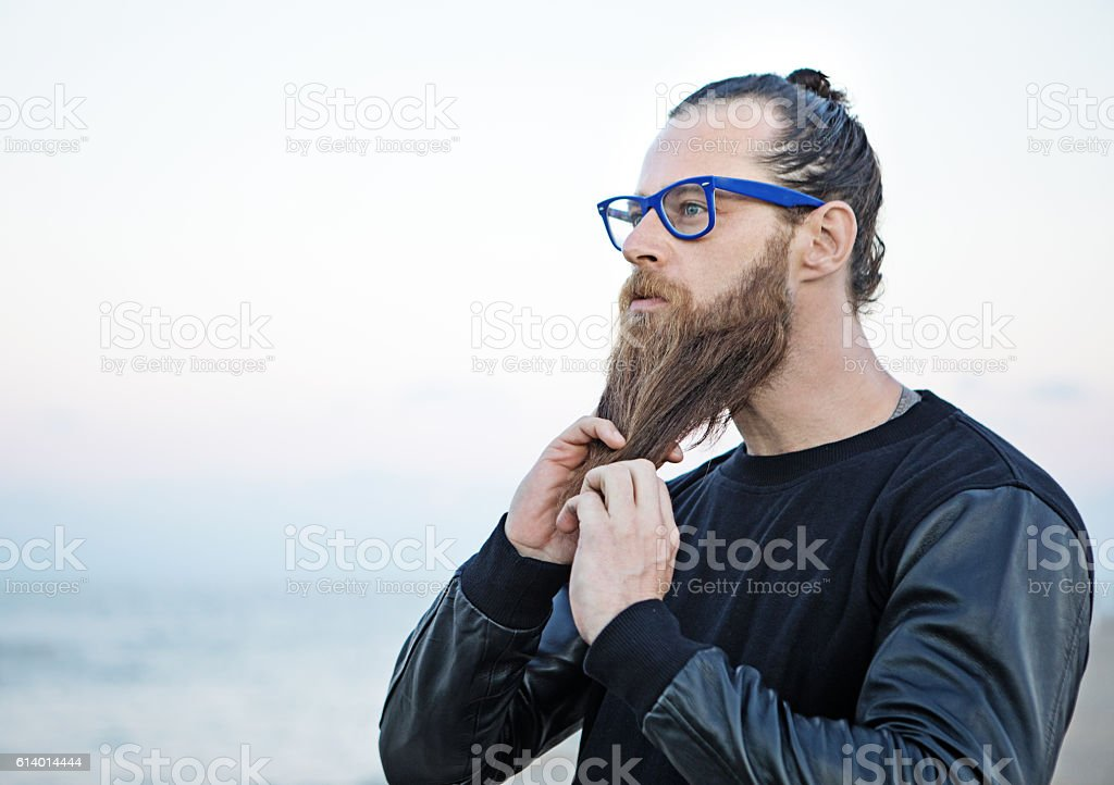 Bespectacled bearded handsome male posing by the sea stock photo