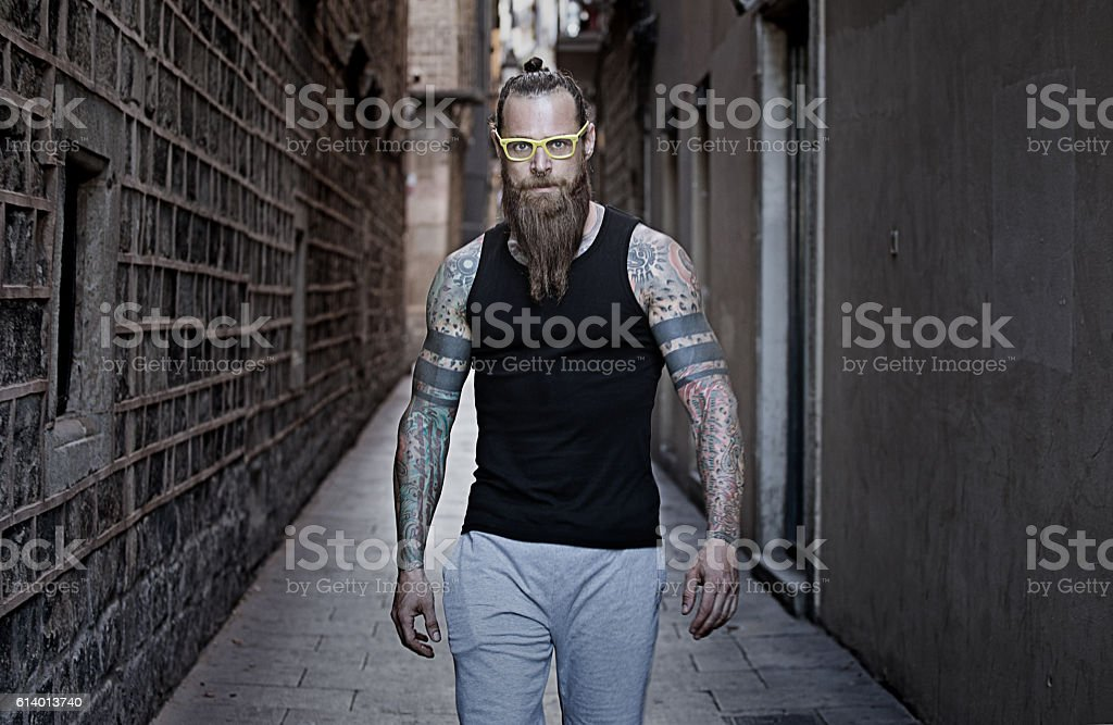 Bespectacled bearded handsome male posing in an urban setting stock photo