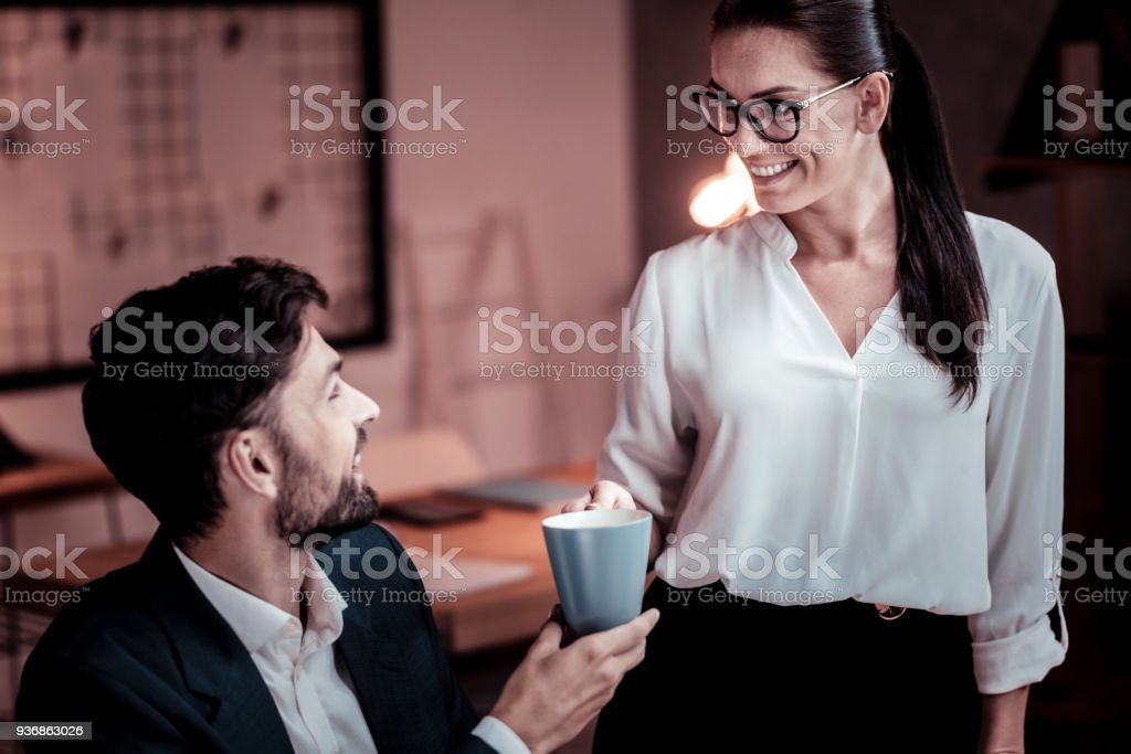 Bespectacled satisfied woman smiling and bringing tea stock photo