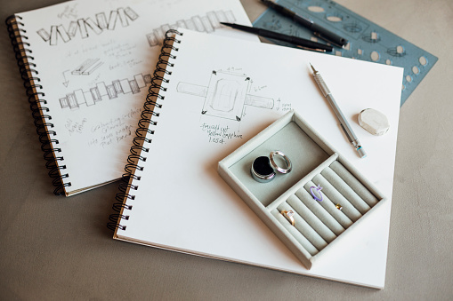 A close-up of a jewellers sketches and designs for a bespoke ring, a prototype is in a display box.