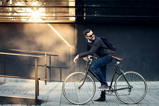 Best city transportation A young stylish businessman going to work by bike. leisure equipment stock pictures, royalty-free photos & images