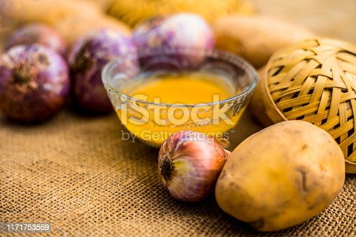 Best earth growth-boosting potion consisting of ingredients which are potato juice and onion juice in a glass bowl along with raw potato and onion on the surface.