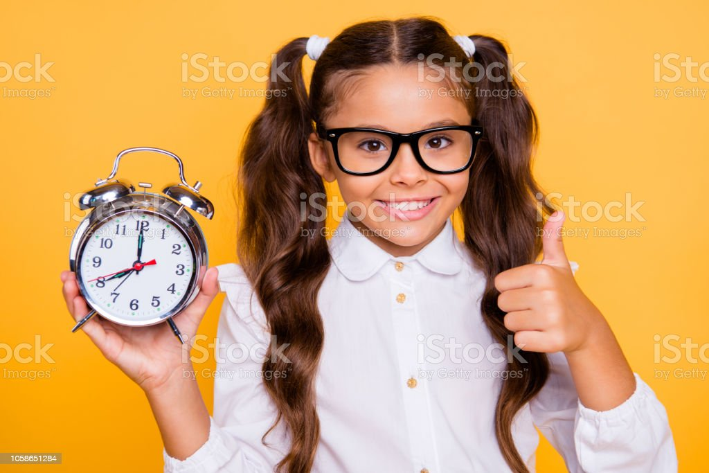 Best free time advertising concept. Close up portrait of confident, pretty, charming, lovely, sweet, gorgeous, small girl isolated on yellow background with big alarm clock in her hands show or give thumbs up stock photo