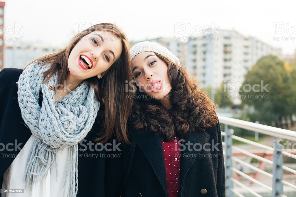 Best friend girls gesturing to camera stock photo
