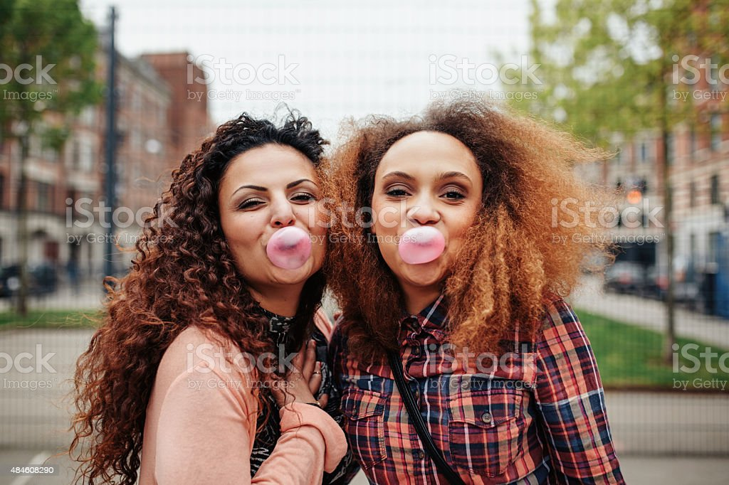 Best friends chewing bubble gum stock photo