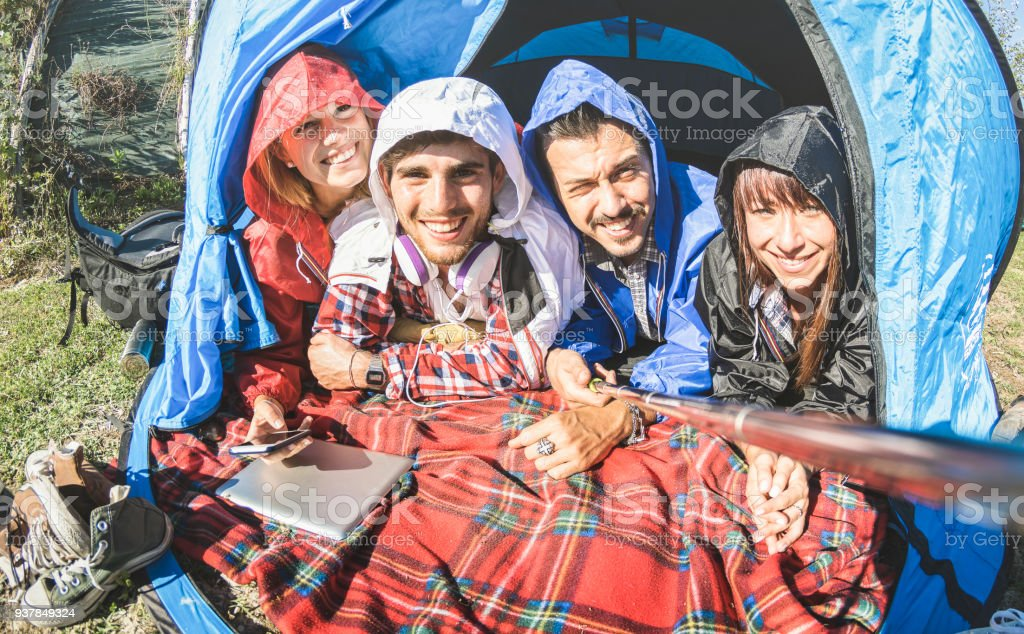 Best friends couples taking selfie at camping tent on sunny day after...