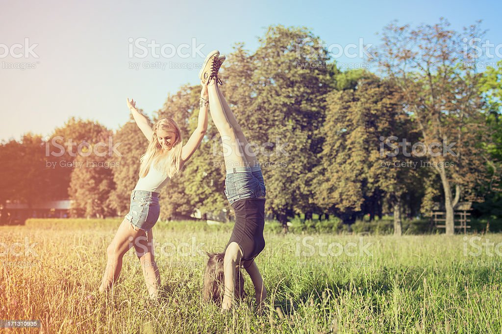 Best friends doing cartwheels in the park stock photo