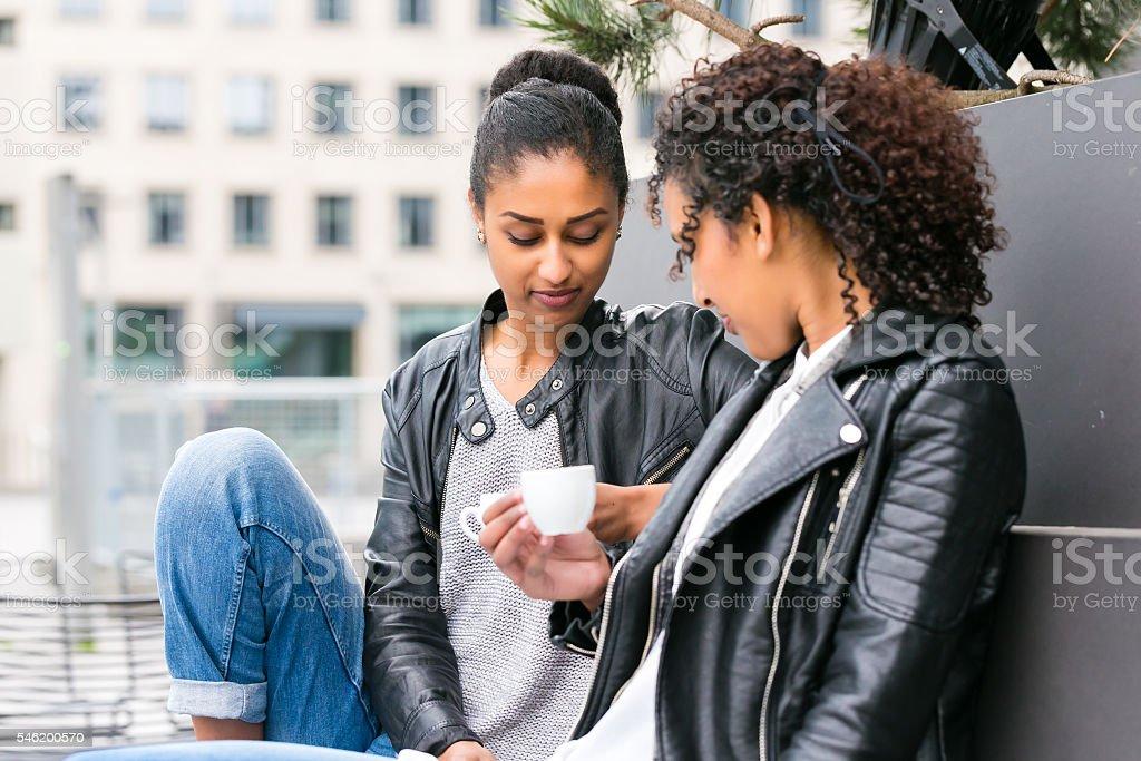 Best friends drinking coffee in city stok fotoğrafı