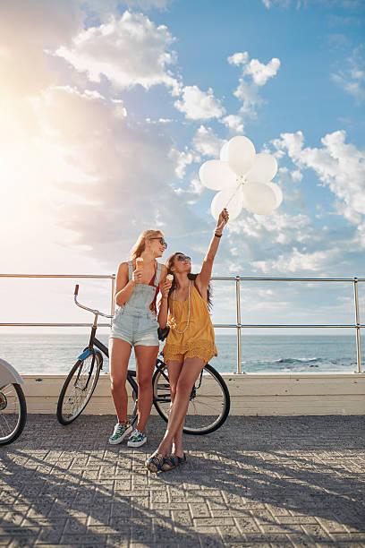 best friends enjoying a day on seaside promenade - eis ballons stock-fotos und bilder