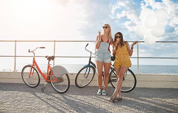 best friends enjoying a holiday on seaside promenade - eis ballons stock-fotos und bilder