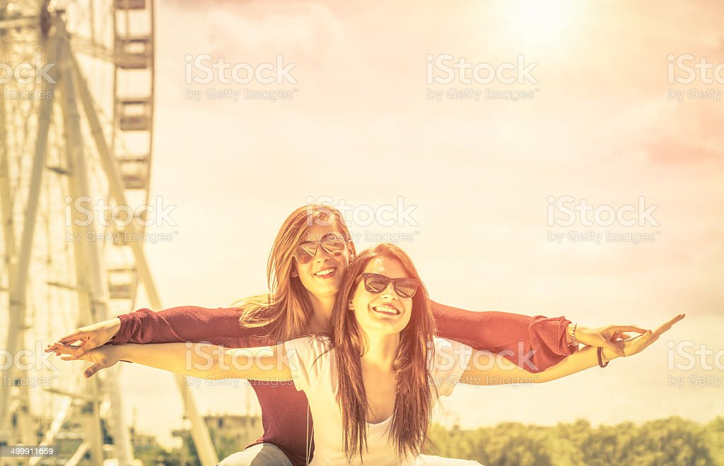 Best friends enjoying time together outdoors at ferris wheel stock photo