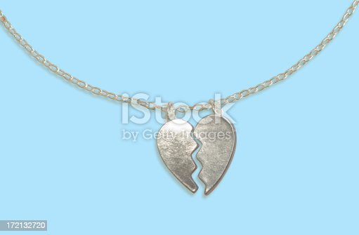 A silver broken heart pendant on a blue background