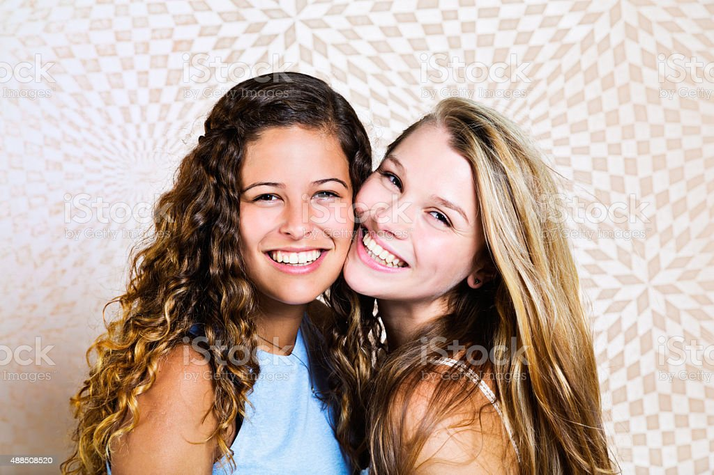 Best friends forever! Two pretty teenage girls pose together, smiling stok fotoğrafı