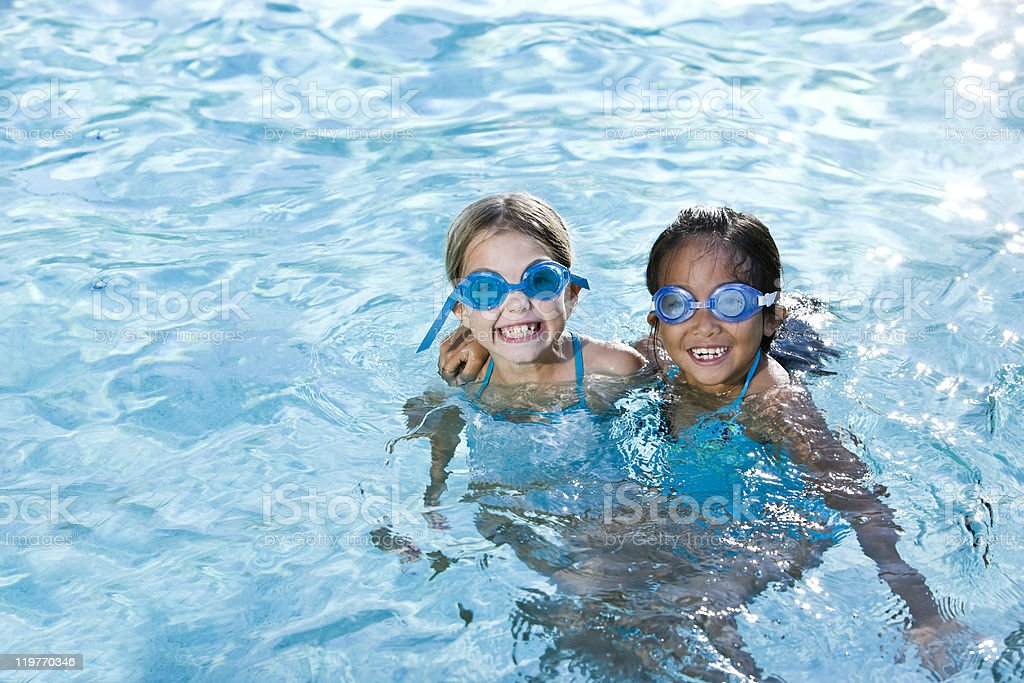 Best friends, girls smiling in swimming pool stock photo