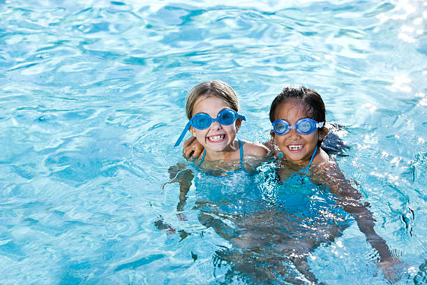 best friends, girls smiling in swimming pool - swimmingpool kids stockfoto's en -beelden
